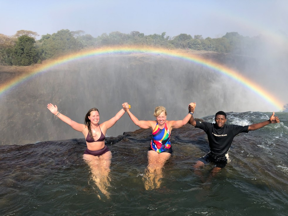 three people holding hands under a rainbow at the top of a waterfall