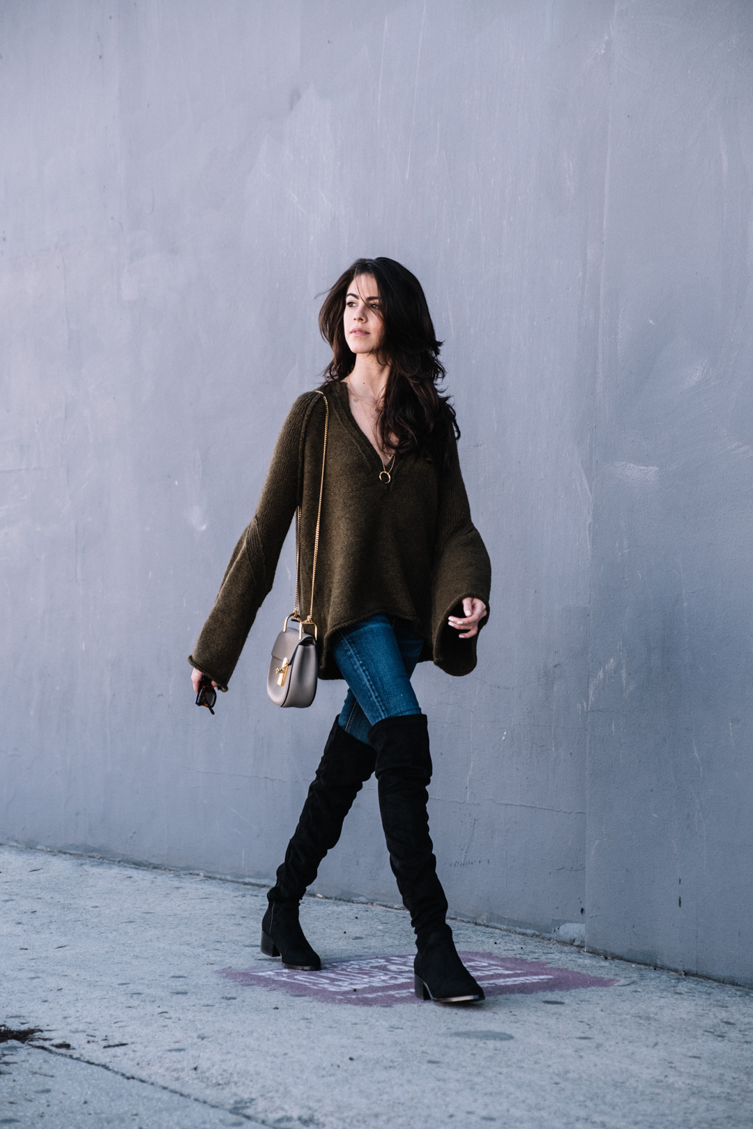 Jackie Roque styling a free people bell sleeve sweater, rag and bone jeans, over the knee boots and a gorjana necklace.