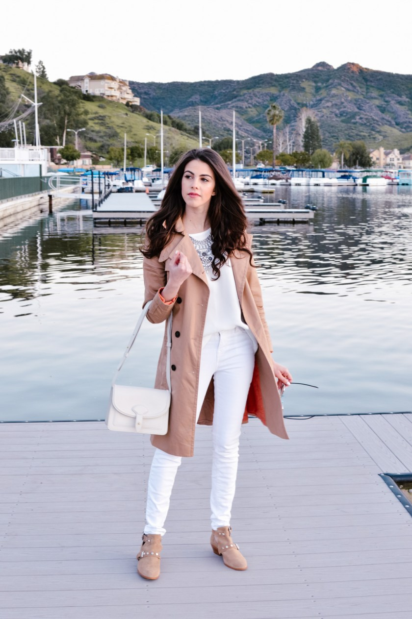 Jackie Roque styling a white on white look with J Brand white jeans, Madewell top, trench coat, and Maiyet white bag.