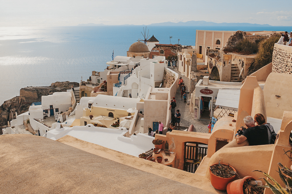 dasynka-fashion-blog-blogger-influencer-inspiration-shooting-model-globettrotter-travel-girl-lookbook-instagram-long-hair-street-style-casual-italy-lifestyle-outfit-poses-santorini-greece-island-vacation-view-caldera-blue-thira-fira-oia-hotel-white-blouse-shorts-bag-mykonos-ideas-summer