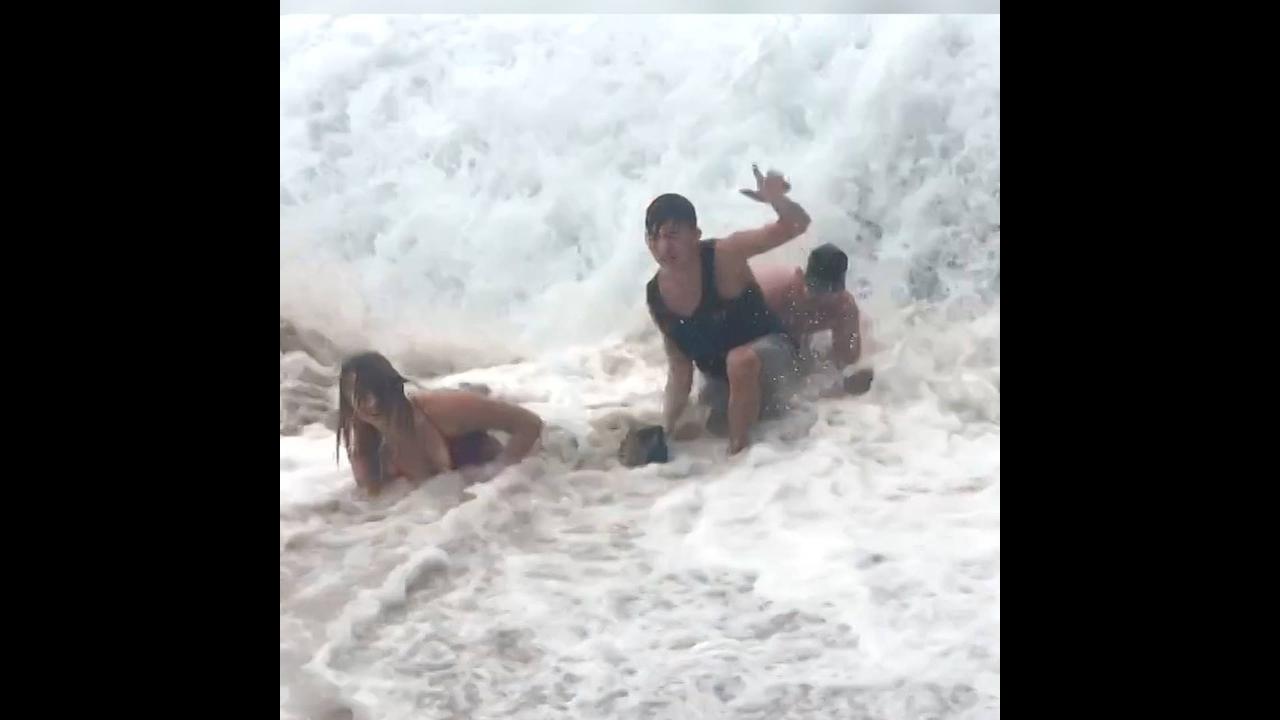 Pessoas sendo traídas pelo mar e pela areia