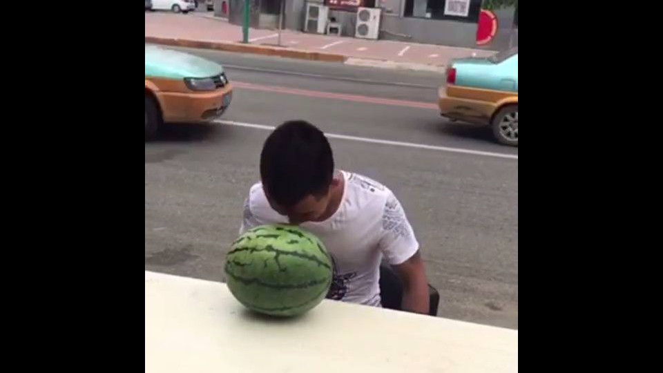 Homem tentando abrir uma melancia com a cabeça