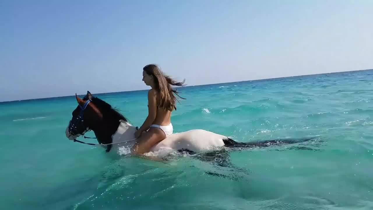 Mulher andando a cavalo em águas límpidas