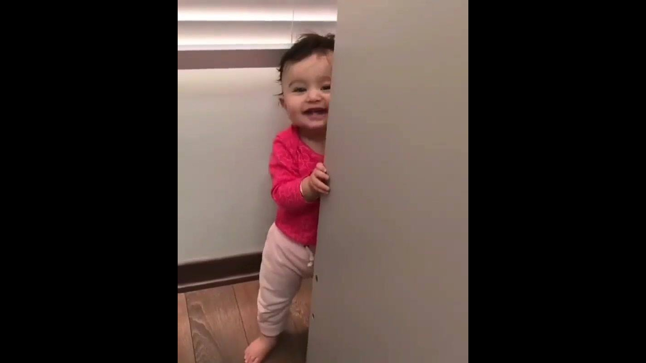 Bebê brincando de esconder da mamãe