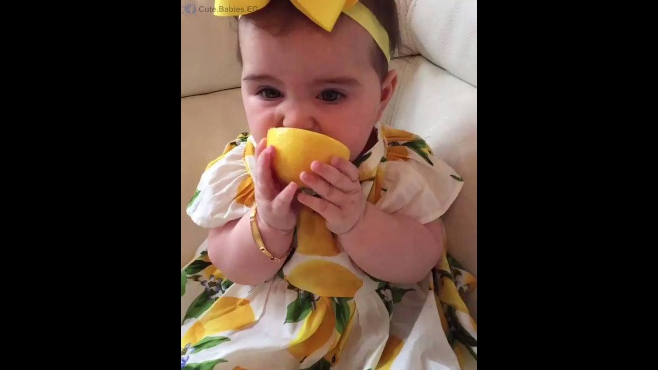 Bebê chupando laranja com as próprias mãozinhas