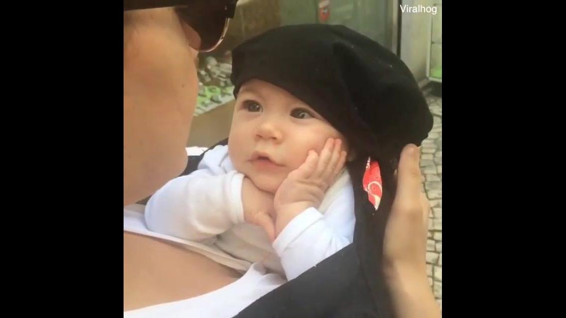 Bebê com mão no rosto ouvindo a mamãe cantar