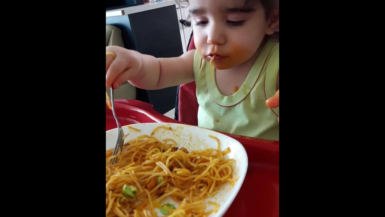 Bebê comendo macarronada com a mão