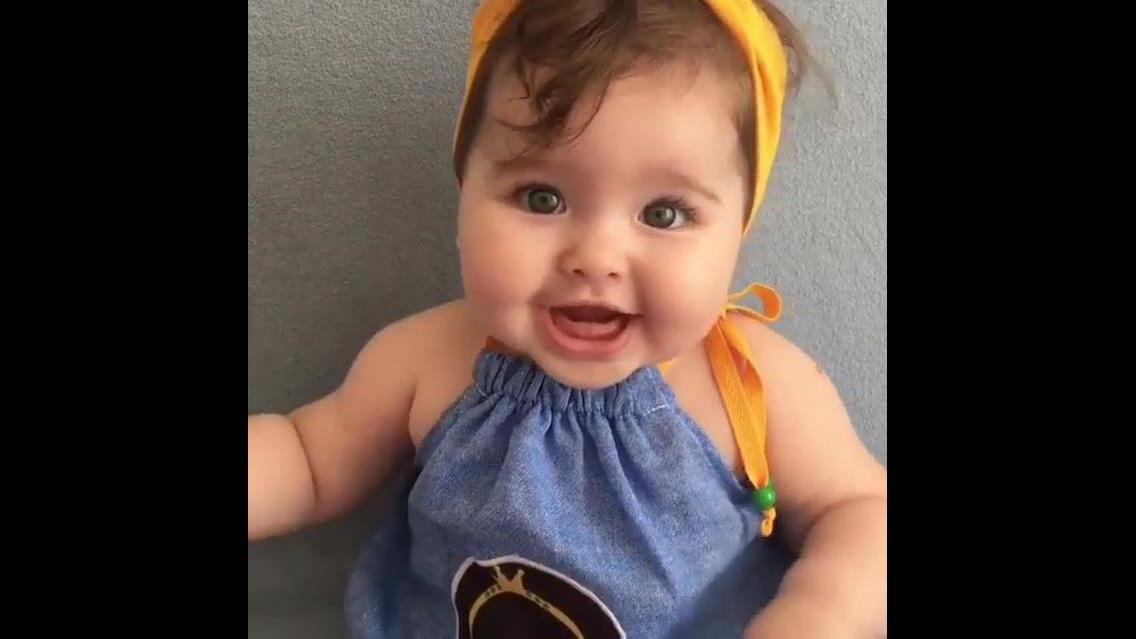 Bebê dando risadinhas fofas, que faixazinha amarela linda na cabeça!!!