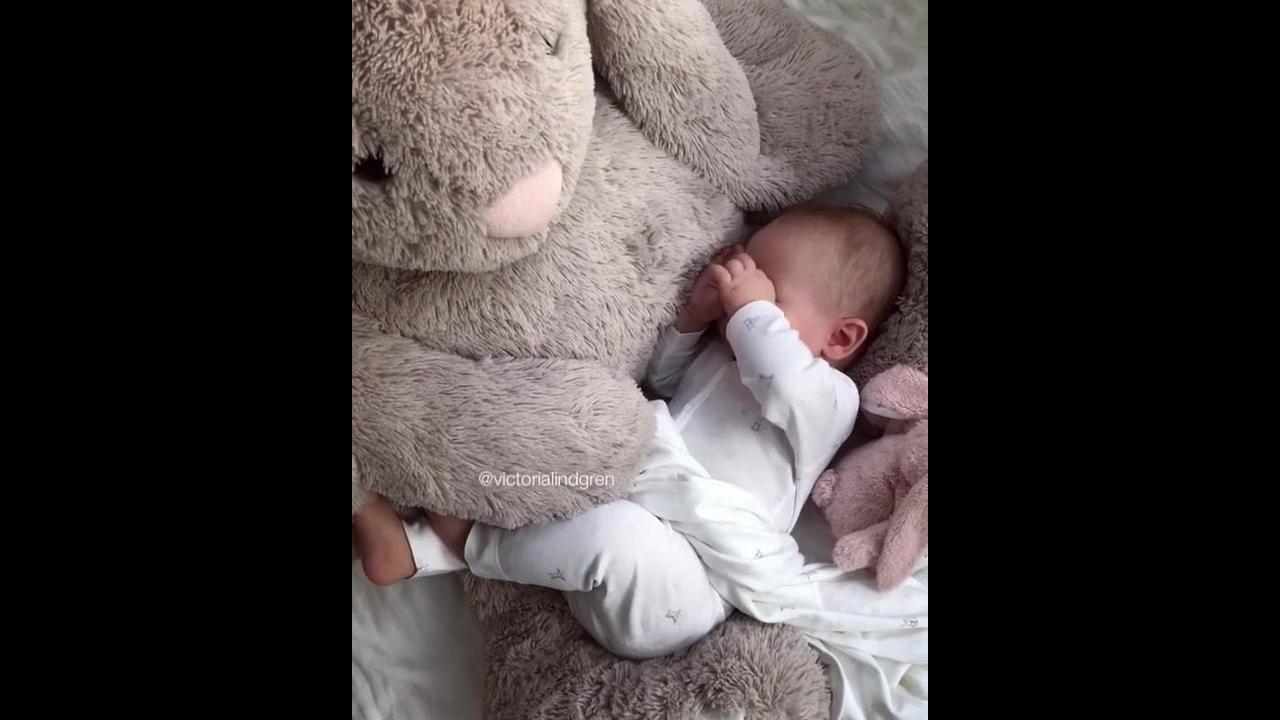 Bebê dormindo no colo de seu gigante coelho de pelúcia