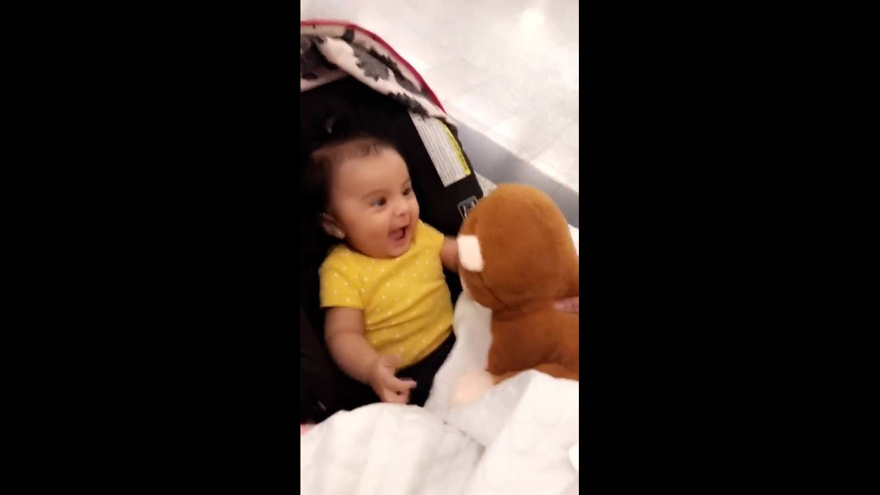 Bebê fica super alegre ao ganhar um ursinho de pelúcia