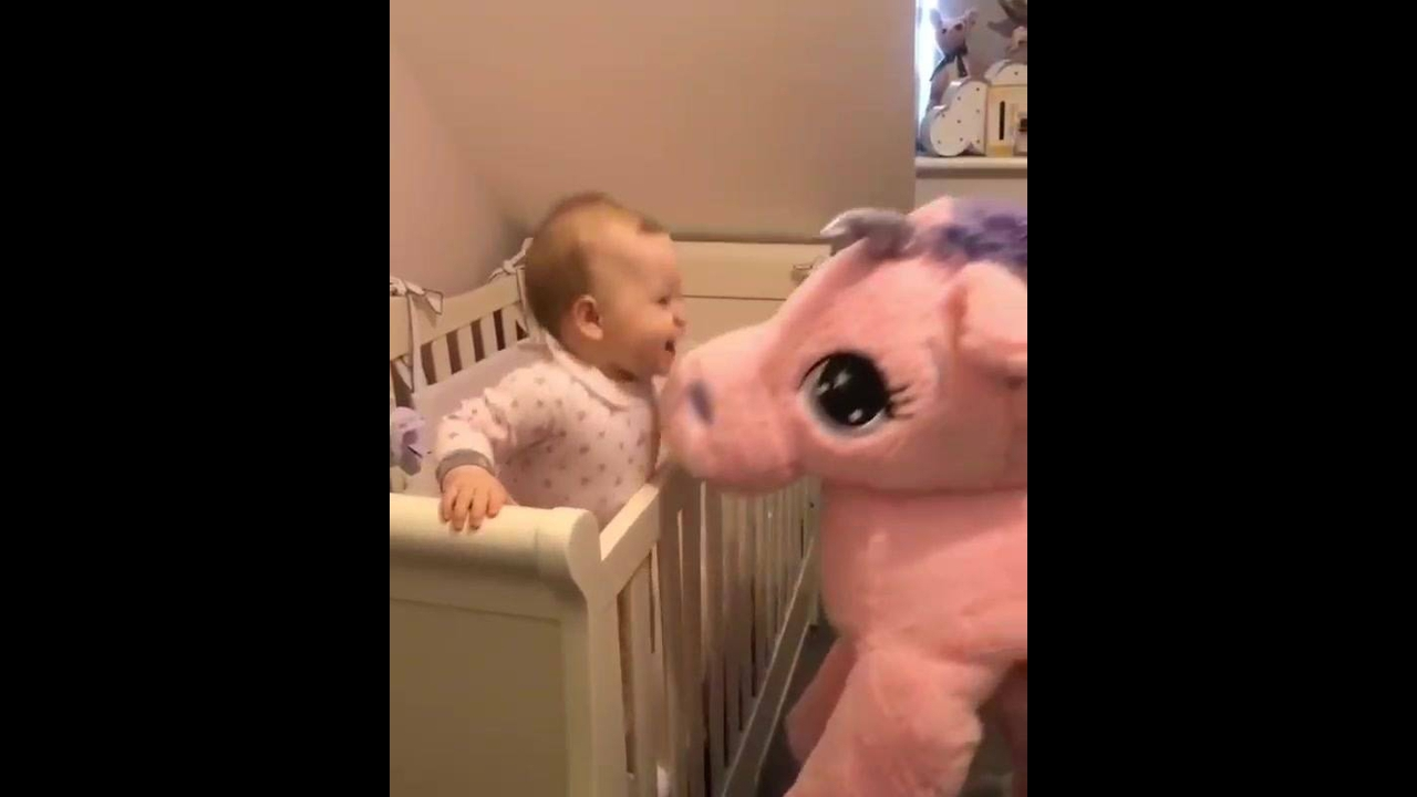 Bebê ganhando muitos beijos de um Unicórnio de pelúcia