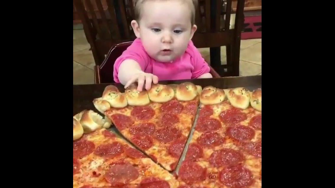 Bebê pegando pedacinho de pizza