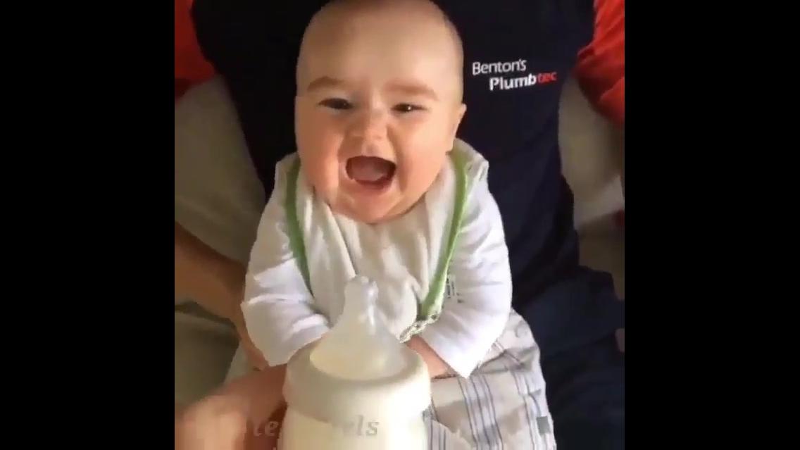 Bebê super alegre na hora de pegar a mamadeira