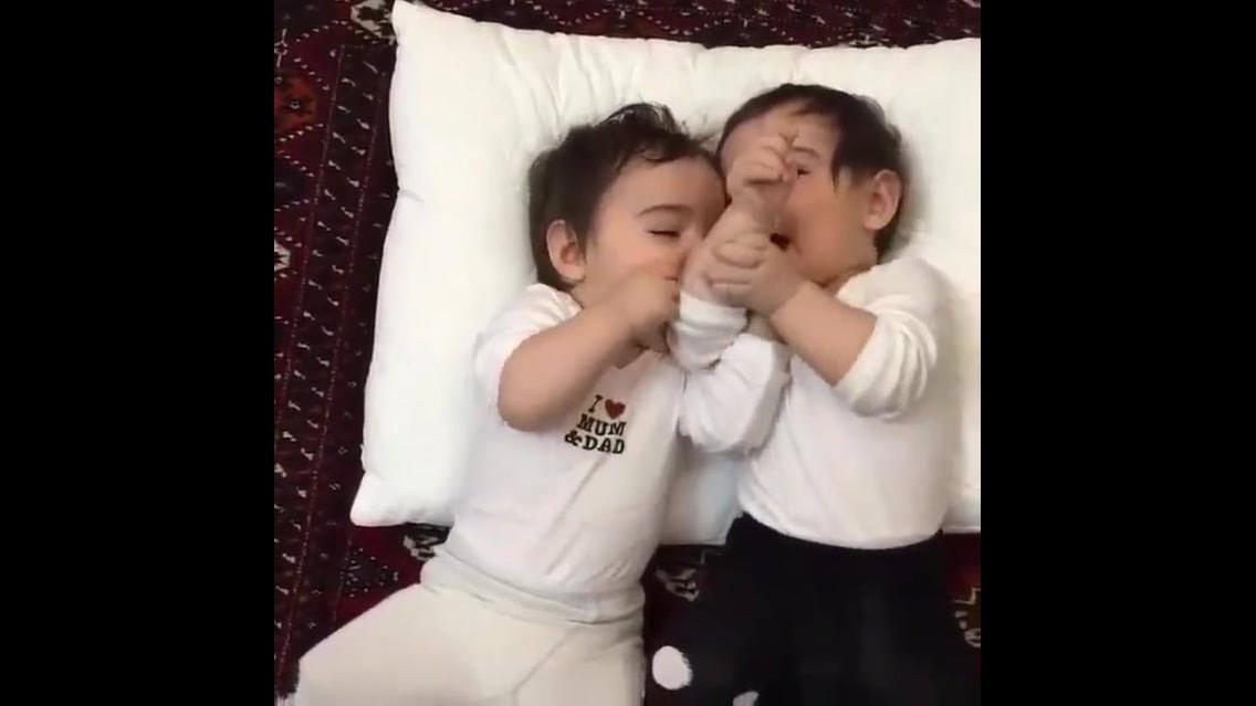 Bebês gêmeos brincando de fazer barulhinhos com a boca