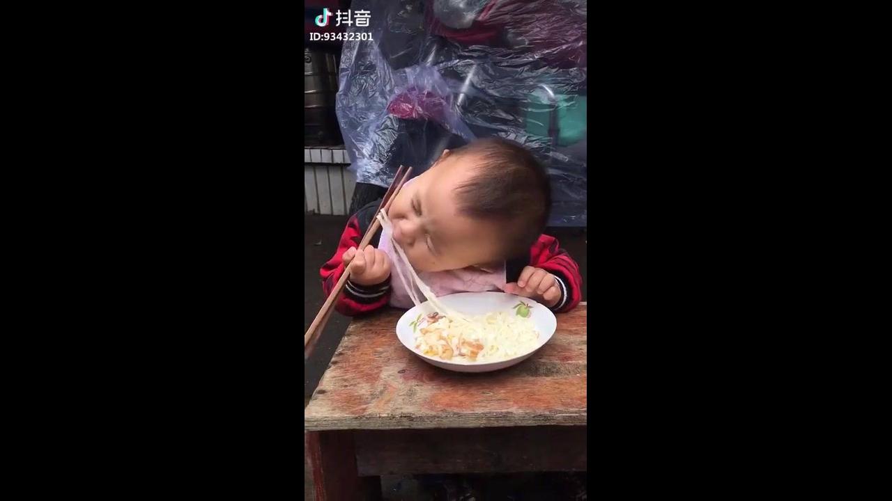 Criança comendo com palitos
