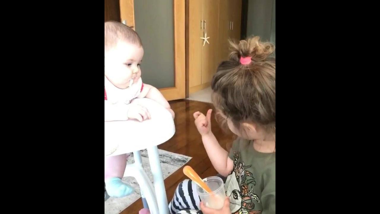 Garotinha dando papinha para irmãzinha