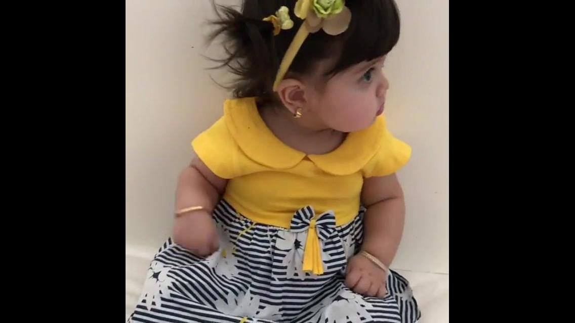 Menina bebê com roupinha amarela e flor na cabeça