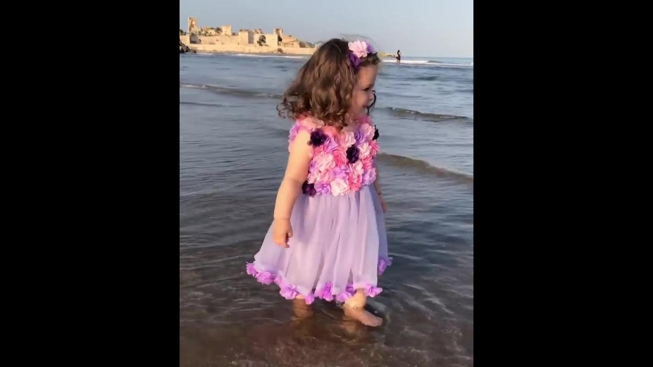 Menina com roupa de princesa na praia