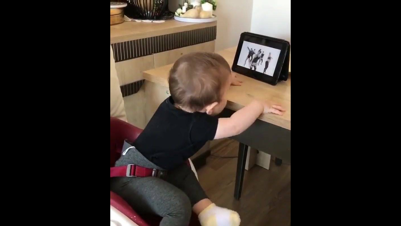 Criança assistindo dança no Tablet e imitando passinhos