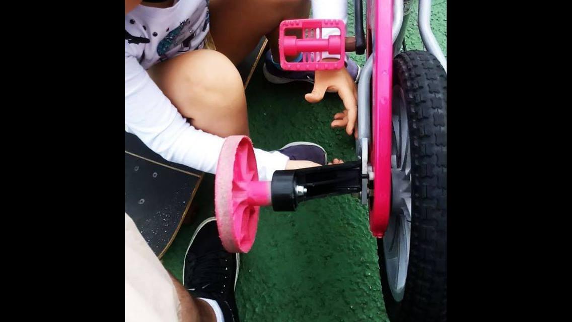 Criança brincando de bicicleta, ela é uma fofura