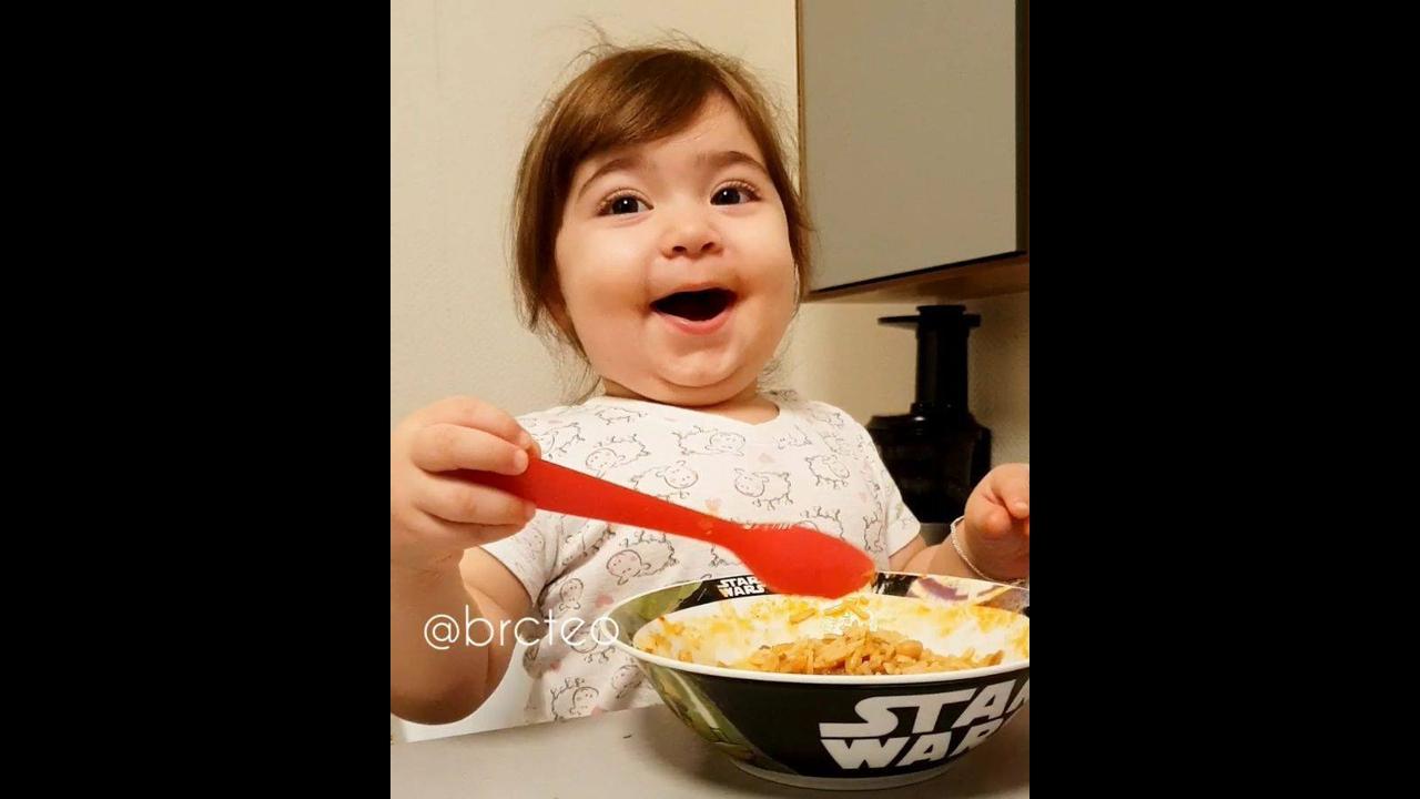 Criança comendo e batendo palma