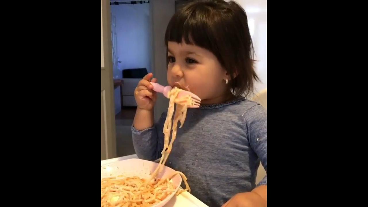 Criança comendo espaguete com molho