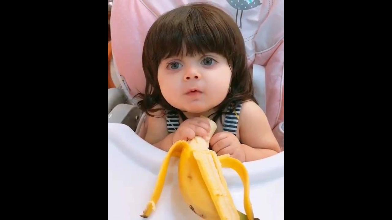Criança comendo fruta com uma carinha muito feliz