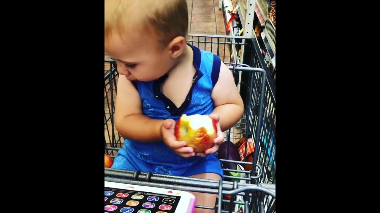Criança comendo maçã em carrinho de supermercado