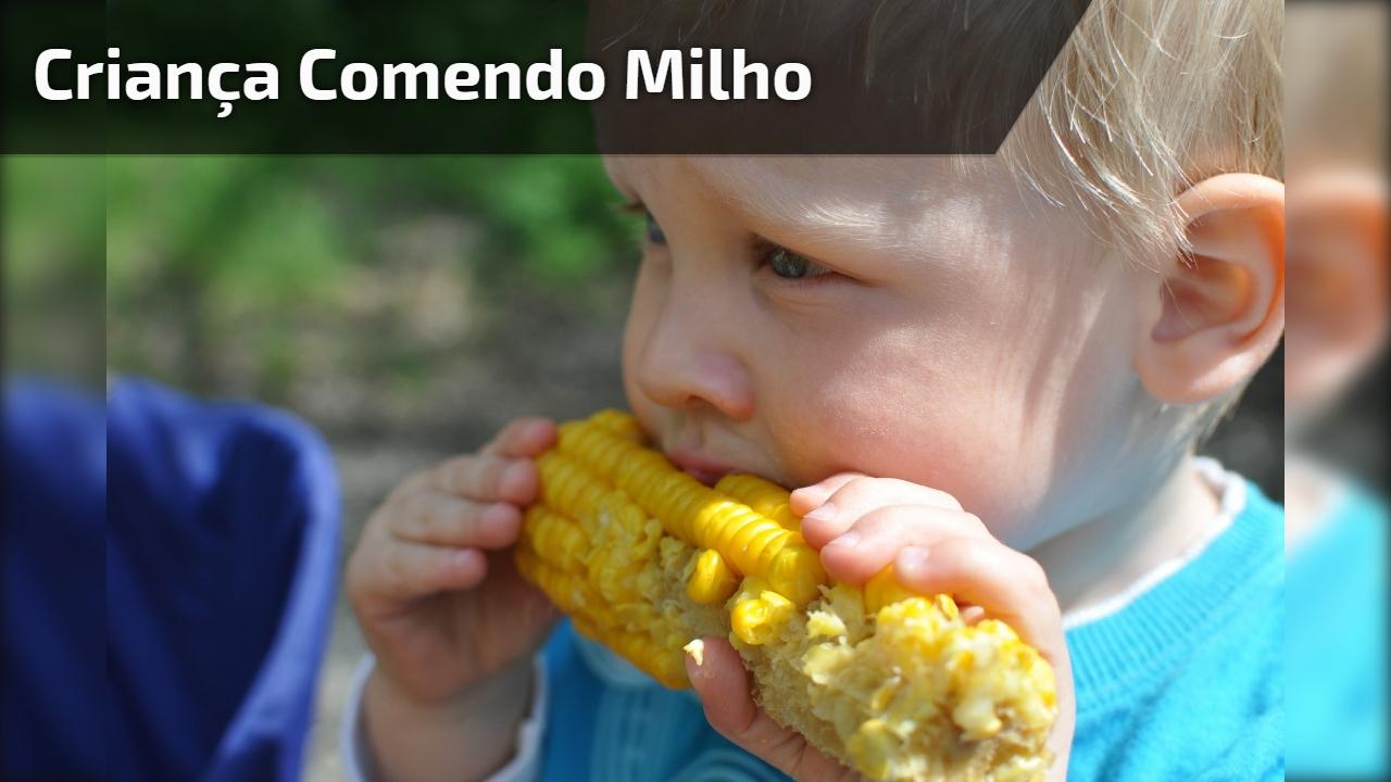 Criança comendo milho
