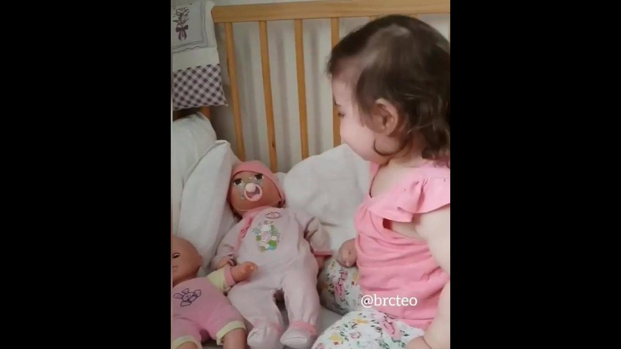 Criança dando boa noite para suas bonecas