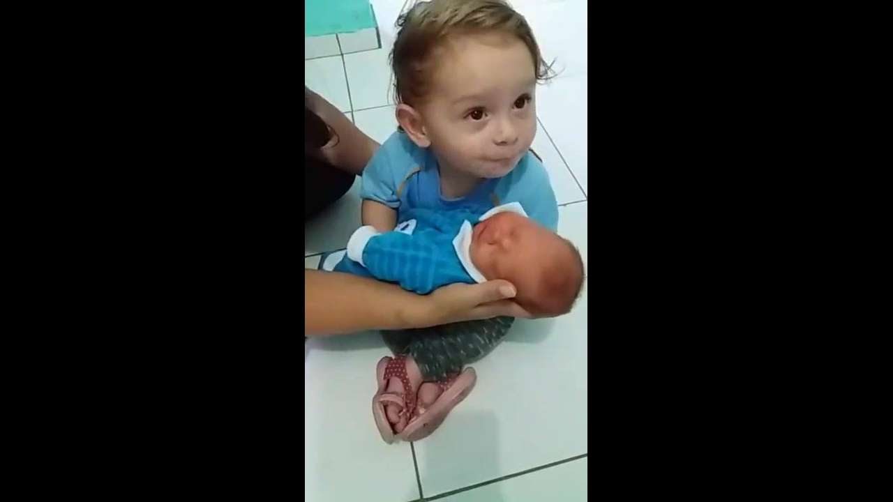 Garotinha chora para poder pegar o irmão recém nascido