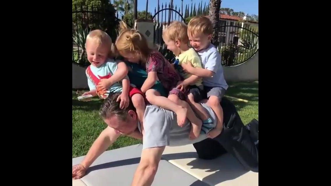Homem brincando de cavalinho com 5 crianças