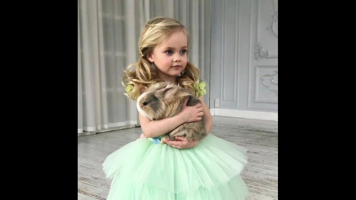 Menina com coelho na mão e vestida como uma princesa