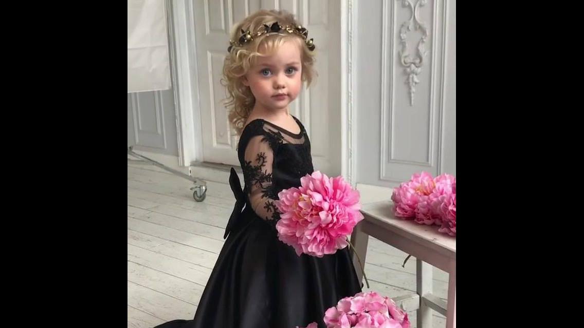 Menina linda com vestido preto e buquê de flores rosas