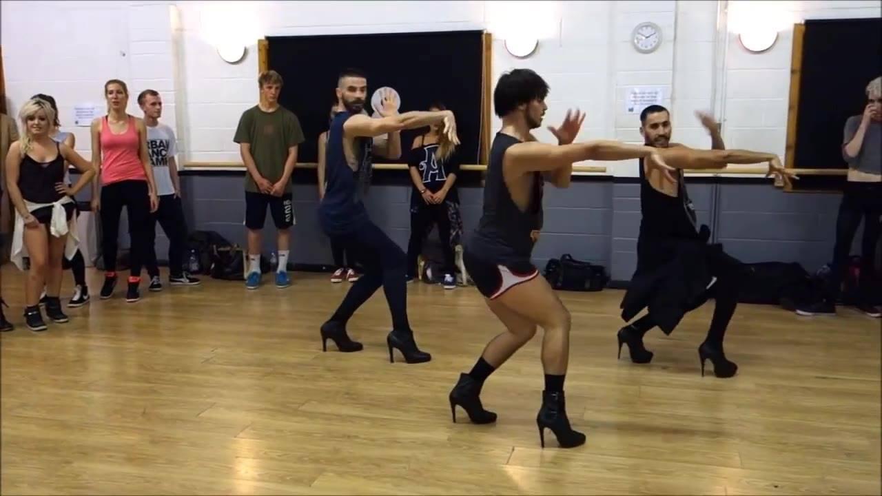 Trio de homens fazendo apresentação de dança com salto