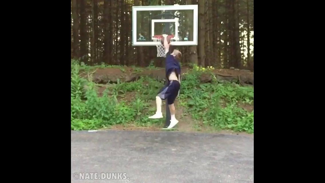 Menino consegue passar a bola por debaixo do corpo e depois fazer a cesta