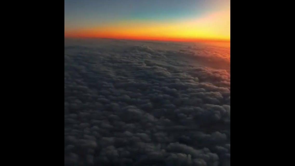 Impressionante céu visto de dentro de um avião em pleno por do sol