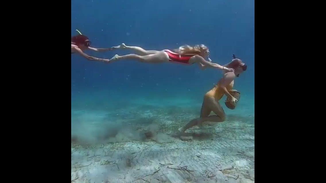 Mulher mergulha, pega uma pedra, e começa a andar
