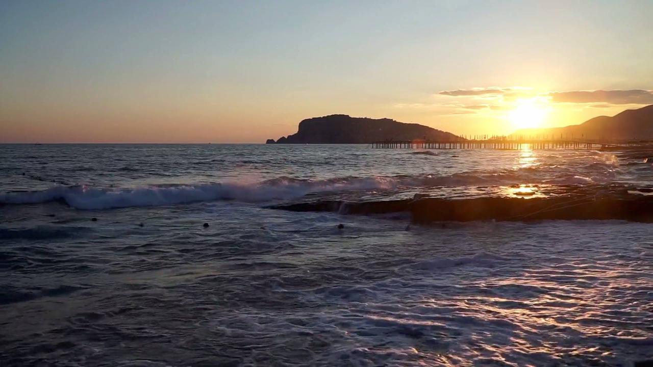 Vídeo com lindo por do sol com as lindas ondas do mar sobre a areia