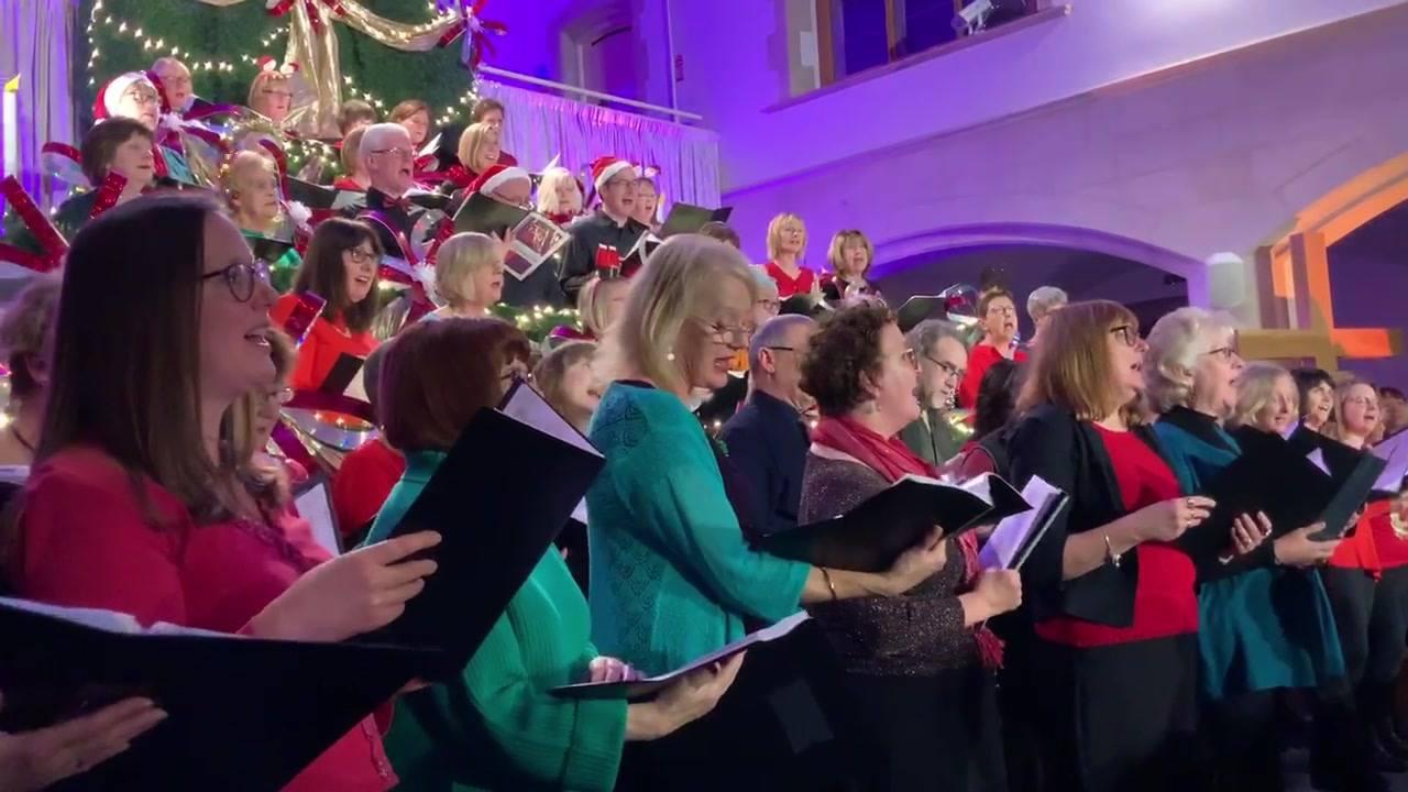 Pessoas cantando no coral a musica mais ouvida no natal