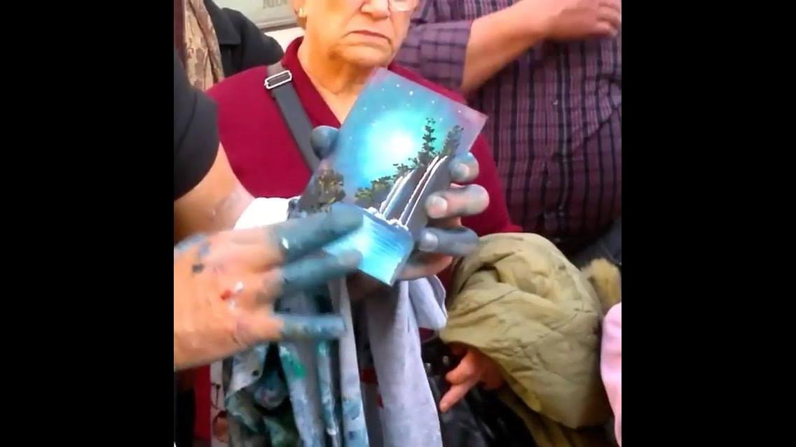 Vídeo com artista pintando paisagem com as mãos