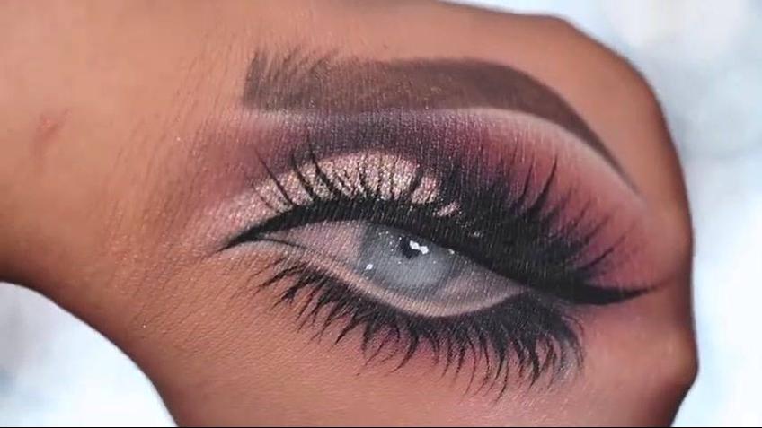 Desenho de olhos maquiados no dorso da mão