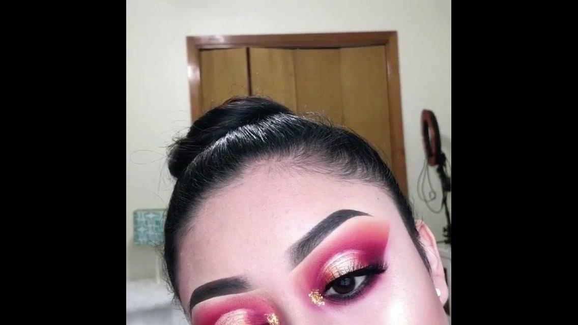 Maquiagem com esfumado vermelho e sombra cintilante na pálpebra móvel