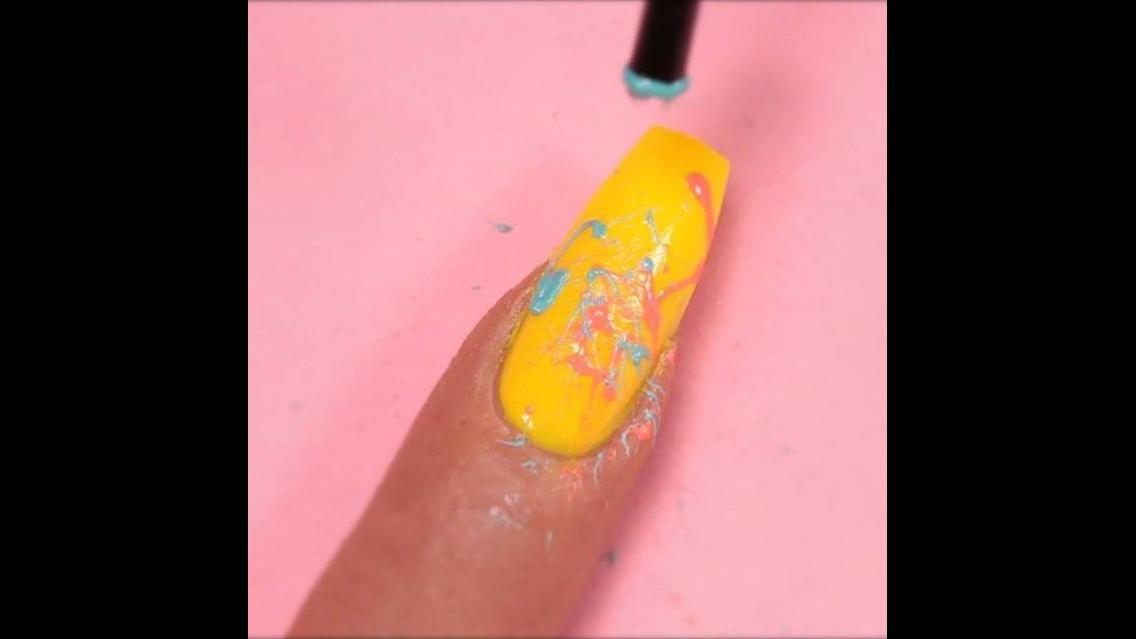 Unha amarela decorada com respingos de outras cores de esmalte