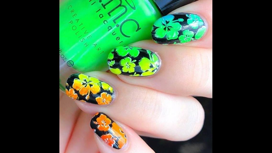 Unha com esmalte preto e carimbo de flores verde e amarelo