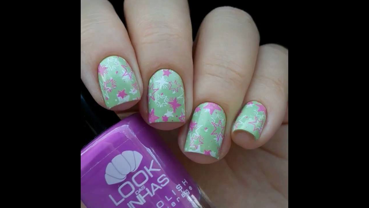 Unha com esmalte verde clarinho e desenho de estrelinhas na cor rosa e branco