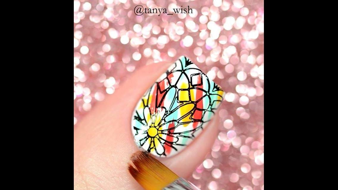 Unha decorada com esmaltes coloridos e carimbo com desenho de flor