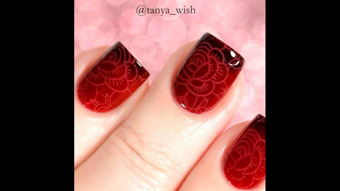 Unhas vermelhas com desenhos e pontas mais escuras