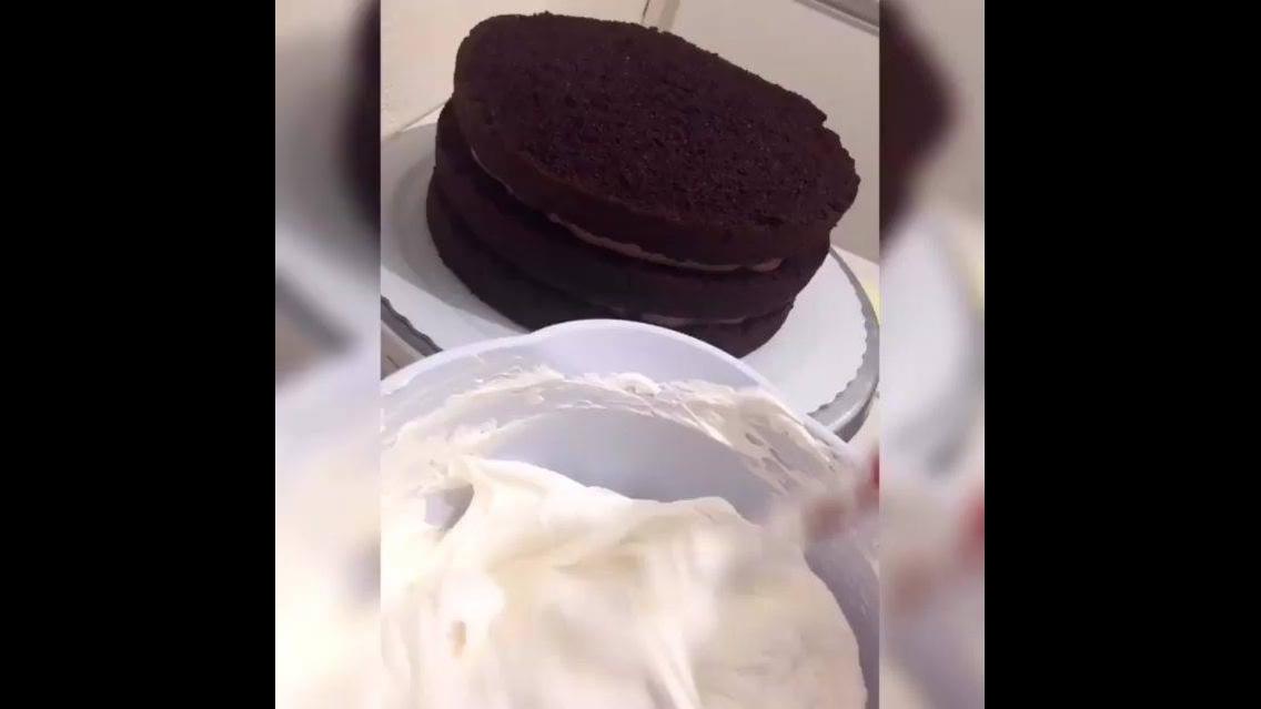 Bolo de chocolate com cobertura branca e detalhes de chocolate