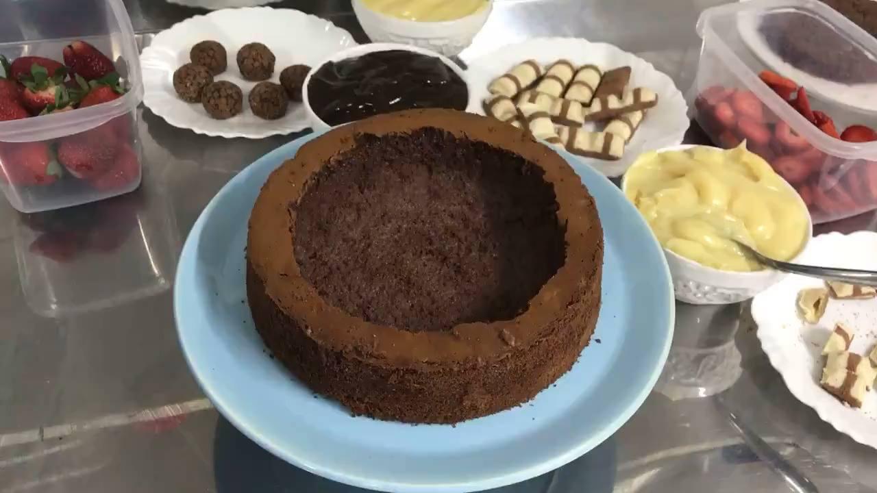 Bolo de chocolate recheado com morangos, bombons e creme, que delicia!